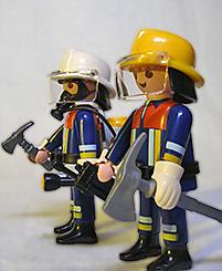 Deux valeureux pompiers, la hache à la main, prêts à secourir la veuve et l'orphelin.